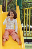 Girl on the slide. Cute smiling child sliding down on yellow slide at playground whilst eating a biscuit Royalty Free Stock Photography
