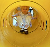 Girl in Slide. A little girl playing sliding down a tubular yellow slide in a park Stock Images