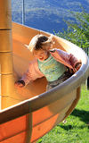 Girl on slide. Smiling little girl falls from the slide Royalty Free Stock Photo