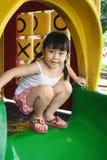 Girl on slide. Girl squatting on the slide Stock Images
