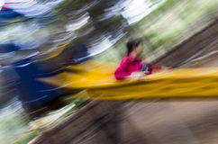 Blur Girl on the slide. Blur image colorful of a girl sliding in a yellow slide Stock Image
