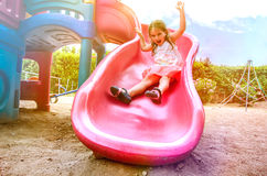 Girl on Slide. Happy Girl on Slide on Public Playground royalty free stock photo