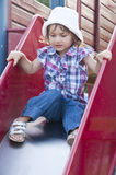 Girl on slide at playground Stock Photos