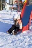 Girl slides down a chute. Little girl slides down hill in winter Stock Photos