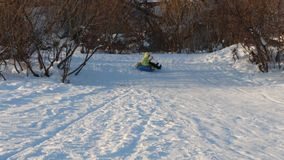 Girl slides on snowtube down from hill at sunny winter day. N stock video