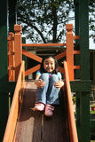 Girl sliding. Happy girl playing slide at the playground in the park on sunny day Stock Photo