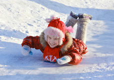 Girl sliding down a frozen hill Royalty Free Stock Photos