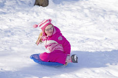 Girl sliding down hill Royalty Free Stock Image