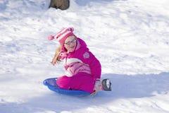 Girl sliding down hill Royalty Free Stock Image