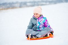 Girl sliding down the hill on saucer sled royalty free stock photos