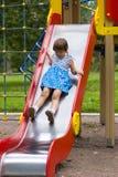 Girl sliding on playground Stock Image