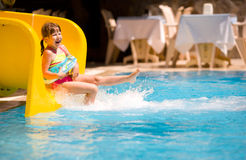 Girl Sliding in pool. Summer holiday Royalty Free Stock Photography