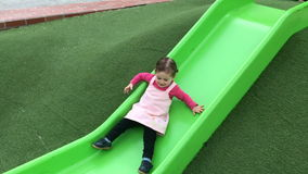 Girl sliding on a slide in the playground stock footage