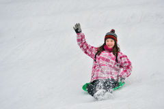 Girl sliding in the snow Stock Images