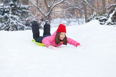 Girl sliding on snow from hill fast. Stock Images