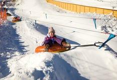 Girl sliding up on snow tubes Stock Images