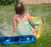 Girl on Slip and Slide. Girl splashing in the water on a slip and slide royalty free stock image