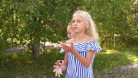Girl Slow Juggle Throw Pine Cone Summer Park Walk. Pretty Caucasian Female Friends Blonde Long Hair Wood Path Stroll. Joyful Children Enjoy Outdoor Nature stock video footage
