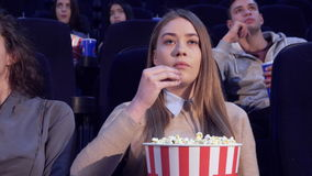 Girl slowly puts the popcorn in her mouth at the movie theater stock video footage