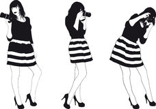 Girl With SLR Photocamera. Slim pretty girl in a striped dress photographed Professional SLR camera Royalty Free Stock Image