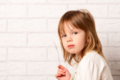 Girl and sly look. Beautiful Girl and sly look. Light feather in her hand. On brick wall background royalty free stock photos