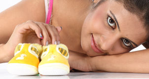 Girl with small baby booties Stock Photography