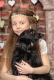 Girl with a small black dog Stock Photos