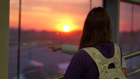 A girl with a son looks out the window in the airport at sunrise, slow motion. A girl with a small cute son in her arms looks out the window at the rising sun stock video