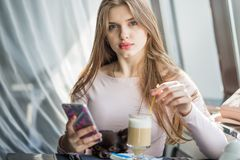 Girl with little dog drinking a latte in a caf? and looking at smartphone Royalty Free Stock Photos