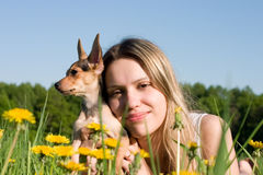 Girl with small doggy. On glade with dandelions Stock Photo