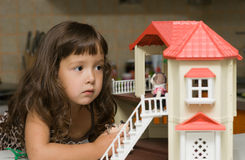 The girl with a small house for dolls. The girl looks at a small house for dolls Stock Image