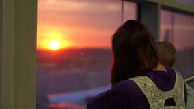 A girl with a son looks out the window in the airport, slow motion at sunrise. A girl with a small son in her arms looks out the window at the rising sun stock video