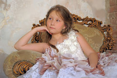 Girl in a smart ball gown sitting in a large armchair Royalty Free Stock Photography