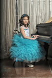Girl in a smart blue dress at the piano Royalty Free Stock Photography