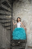Girl in a smart blue dress on stairs in a castle Royalty Free Stock Image
