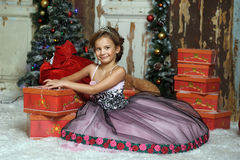 Girl in a smart dress with a lot of gifts at Christmas Royalty Free Stock Photo