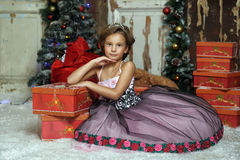 Girl in a smart dress with a lot of gifts at Christmas Royalty Free Stock Photography