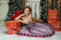 Girl in a smart dress with a lot of gifts at Christmas Stock Photos