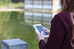 Girl with smart phone in park on a background of lake Royalty Free Stock Photo