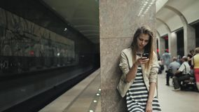 Girl with smart phone at train station. Portrait of a young caucasian woman, looking at the phone while waiting for the. Girl with smart phone at train station stock video