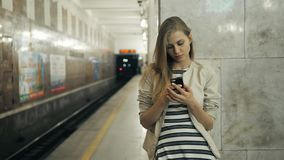 Girl with smart phone at train station. Portrait of a young caucasian woman, looking at the phone while waiting for the. Girl with smart phone at train station stock footage
