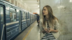 Girl with smart phone at train station. Portrait of a young caucasian woman, looking at the phone while waiting for the. Girl with smart phone at train station stock video footage