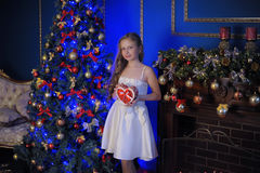 Girl in a smart white dress at the Christmas tree Stock Photography