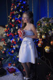 Girl in a smart white dress at the Christmas tree royalty free stock photography
