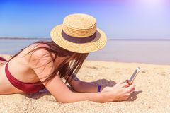 Girl with smartphone on the beach Royalty Free Stock Photos