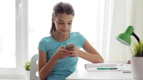 Girl with smartphone distracting from homework stock footage
