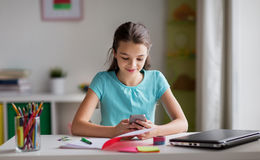 Girl with smartphone distracting from homework Stock Image