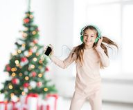 Girl with smartphone and headphones at christmas Stock Photos