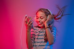 Girl with smartphone and headphones listens to music Royalty Free Stock Photography