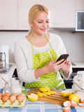 Girl with smartphone at kitchen Royalty Free Stock Photos